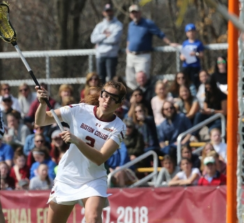 Women's Lacrosse player throwing the ball towards the goal