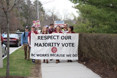 Grad students carrying a banner that says : RESPECT OUR MAJORITY VOTE. BC WORKS BECAUSE WE DO.