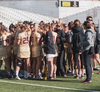 BC womens Lax team in a huddle, looking happy after a GREAT win against yale.