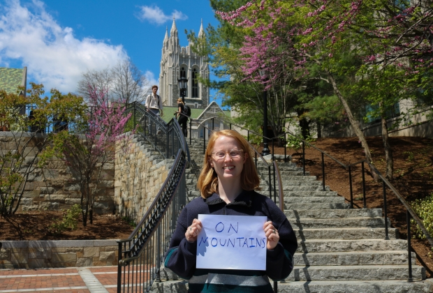 """Caroline standing on the million dollar stairs, gasson in the background, with an """"on mountains"""" sign."""