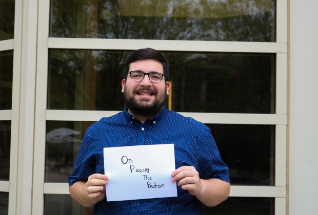 Nick standing with a sign in front of Vandy Cabaret room, saying On Passing the Baton