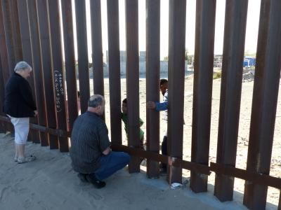 Man speaking to kids through the border wall