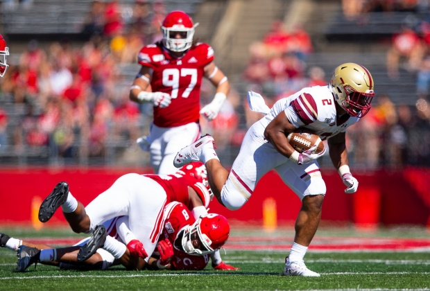 BC football player running over two colliding rutgers players
