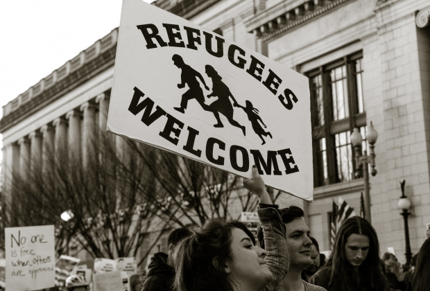 """Woman holding sign reading """"refugees welcome."""""""