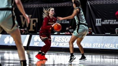 BC Women's Basketball player gets ready to pass as a Wake Forest player blocks her.