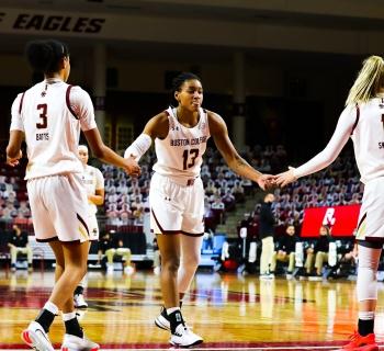 Women's Basketball teammates highfiving after a play