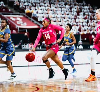 BC Womens basketball in pink uniforms running down the court against Pitt